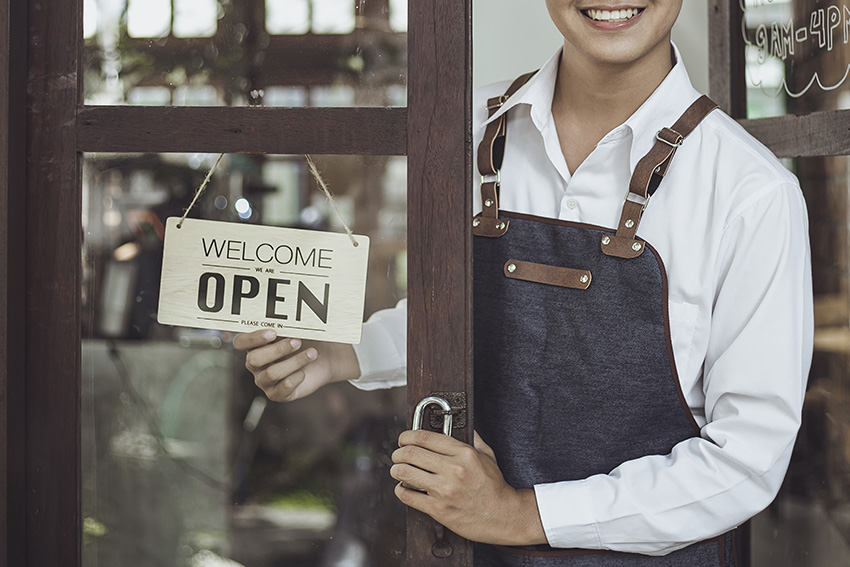 Store owner turning open sign broad through the door glass and r
